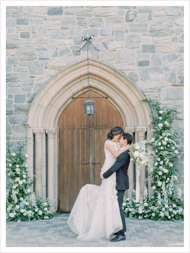Bride and groom in front of ceremony arch