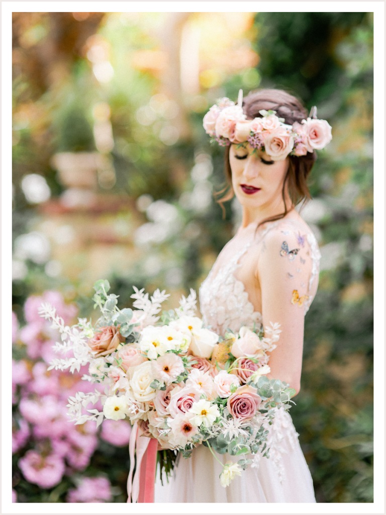 Bride during bridal portraits wearing a flower crown and holding a floral bouquet